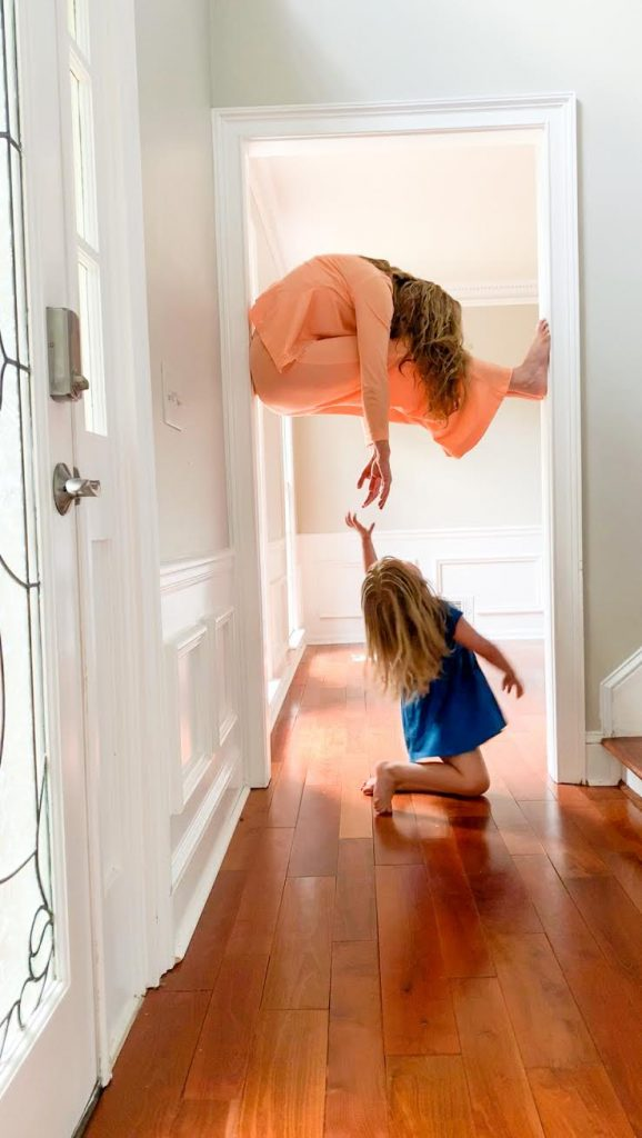 A woman is propped up in a doorway. Her daughter reaches for her from below.