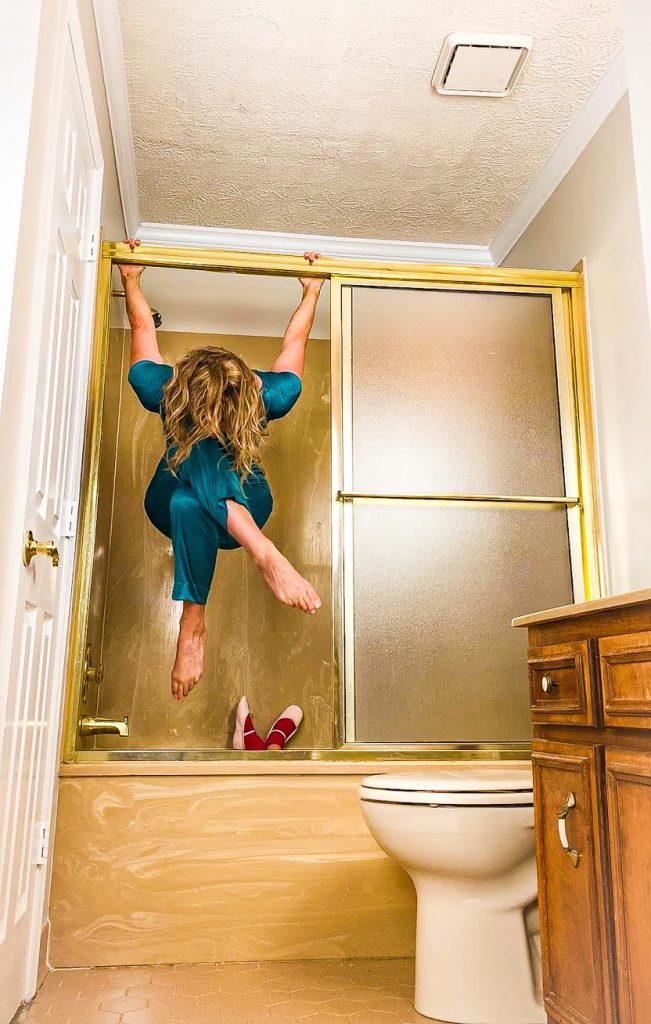 A woman hangs from the frame of her shower door, her child's feet visible below.