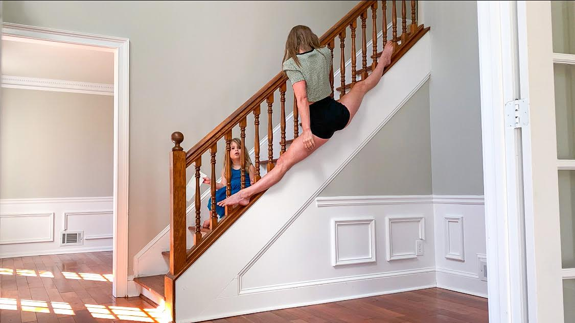 A woman holds onto the bannister of the staircase while her daughter looks on.